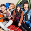 Happy people sitting near the tent with guitar — Stock Photo #55521523