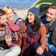 People sitting at the riverbank and playing guitar — Stock Photo #55521587