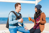 Young man and woman drinking beer on beach — Foto Stock