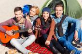 Happy people sitting near the tent with guitar — Stock Photo