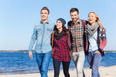 Happy people walking by the beach together — Stock Photo