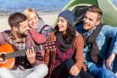 Люди, сидящие в береге реки и играющие на гитаре — Стоковое фото