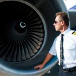 Pilot examining turbine engine of airplane — Stock Photo #55976491