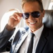 Businessman sitting at his seat in airplane — Stock Photo #55977371