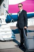 Businessman carrying suitcase near  airplane entrance — Stock Photo