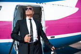 Mature businessman getting out of airplane — Stock Photo