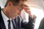 Businessman touching his forehead in airplane — Stock Photo