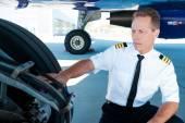 Pilot in uniform examining an airplane wheels — Stock Photo