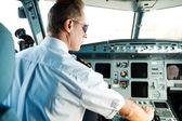 Confident male pilot sitting in cockpit — Stock Photo