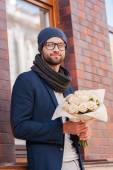 Man in smart casual wear holding bouquet of flowers — Stock Photo