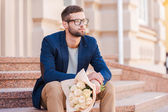 Man in smart jacket holding bouquet — Stock Photo