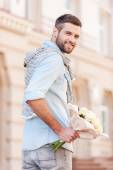 Young man holding bouquet of flowers — Stock Photo