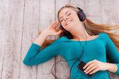 Woman listening to music through headphones — Stock Photo