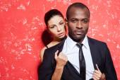 Unleashed desire. Handsome young man in formalwear standing against red background while woman taking off his jacket — Stock Photo