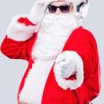 Santa Claus in sunglasses adjusting his headphones — Stock Photo #57614727
