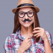 Woman holding fake mustache and glasses — Stock Photo #57752545