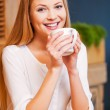 Woman enjoying coffee in cafe — Stockfoto #57857367