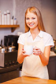 Female barista stretching out fresh coffee — Stock Photo