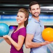 Постер, плакат: Man and woman holding bowling balls