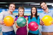Friends outstretching bowling balls — Stock Photo