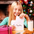 Little girl putting letter to Santa into the envelope — Stock Photo #58008873