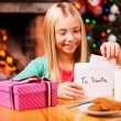 Little girl putting letter to Santa into the envelope — Stock Photo #58008899
