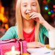 Little girl eating a cookie near Christmas Tree — Stock Photo #58008915