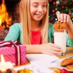 Little girl soaking cookie in milk near Christmas Tree — Stock Photo #58008919