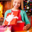 Little girl opening gift box near Christmas Tree — Stock Photo #58008939