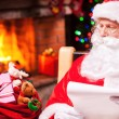 Santa Claus looking at his sack with presents — Stock Photo #58009071