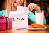 Little girl putting letter to Santa into envelope — Stock Photo