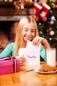 Little girl putting letter to Santa into the envelope — Stockfoto