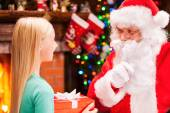 Little girl holding gift box and looking at Santa Claus — Stock Photo