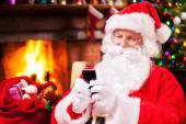 Santa Claus typing message on mobile phone — Stock Photo