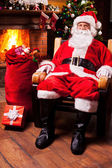 Santa Claus sitting at his wooden chair — Stock Photo