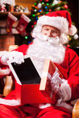 Santa Claus putting digital tablet into gift box — Stock Photo