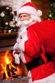 Santa Claus carrying sack with presents — Stock Photo