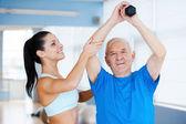 Физиотерапевт, работающий со старшим человеком — Стоковое фото