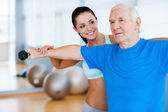 Physical therapist working with senior man — Stock Photo