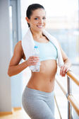 Woman in sports clothing holding bottle with water — Stock Photo