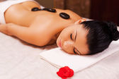 Woman lying on massage table with spa stones — Stock Photo