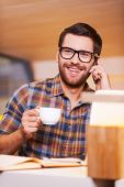 Man talking on the mobile phone and drinking coffee — Stock Photo