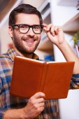 Young man holding book and smiling — Stock Photo