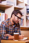 Hombre escribiendo algo en el cojín de nota — Foto de Stock
