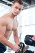 Muscular man choosing weight to lift — Stock Photo