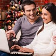 Couple using computer on Christmas — Stock Photo #59294829