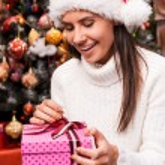 Woman in Santa hat opening gift box — Stock Photo #59295057