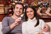 Loving couple watching TV on Christmas — Stock Photo