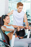 Woman working out in gym with instructor — Stock Photo
