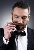 Mature man in formalwear smelling cigar — Stock Photo